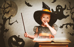 Halloween. cheerful little witch with magic wand and book conjur Stock Photos