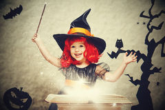 Halloween. cheerful little witch with magic wand and book conjur stock photo