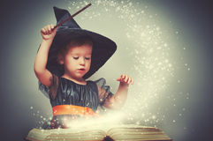 Halloween. cheerful little witch with a magic wand and glowing b. Ook conjure and laughs Stock Photo