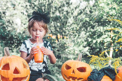 Halloween. Child dressed in black drinking pumpkin cocktail, trick or treat. Little girl near jack-o-lantern decoration in the woo Royalty Free Stock Photography