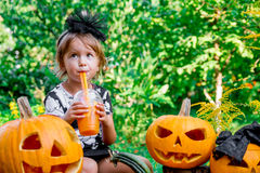Halloween. Child dressed in black drinking pumpkin cocktail, trick or treat. Little girl near jack-o-lantern decoration in the woo Stock Image