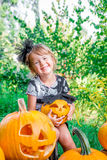 Halloween. Child dressed in black with jack-o-lantern in hand, trick or treat. Happy little girl  pumpkin in the wood, outdoors. Stock Image