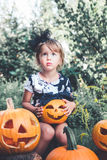 Halloween. Child dressed in black with jack-o-lantern in hand, trick or treat. Little girl  pumpkin in the wood, outdoors. Royalty Free Stock Photo