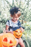 Halloween. Child dressed in black with jack-o-lantern in hand, trick or treat. Little girl  pumpkin in the wood, outdoors. Stock Photo