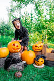Halloween. Child dressed in black with jack-o-lantern in hand, trick or treat. Scaring little girl  pumpkin in the wood, outdoors. Stock Photography