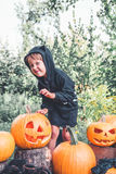 Halloween. Child dressed in black with jack-o-lantern in hand, trick or treat. Scaring little girl  pumpkin in the wood, outdoors. Royalty Free Stock Images