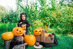 Halloween. Child dressed in black with jack-o-lantern in hand, trick or treat. Smiling little girl  pumpkin in the wood, outdoors. Stock Photography