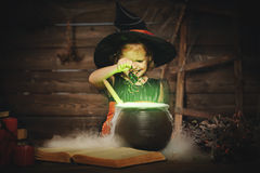 Halloween. child girl witch preparing  potion in cauldron Royalty Free Stock Photography