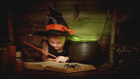 Halloween. child girl witch preparing  potion in cauldron Royalty Free Stock Image