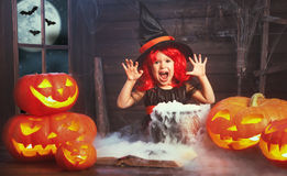 Halloween. child girl witch preparing  potion in cauldron with p Stock Photos