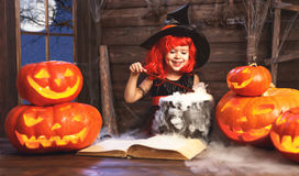 Halloween. child girl witch preparing  potion in cauldron with p Stock Photo