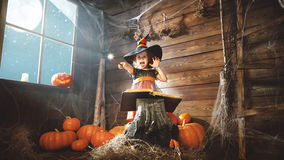 Halloween. child little witch with magic wand and reading a mag. Ical book of spells in the old hut Royalty Free Stock Photos