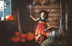 Halloween. child little witch with magic wand and reading a mag. Ical book of spells in the old hut stock image