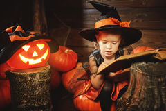Halloween. child little witch with  pumpkin Jack  and magical bo Royalty Free Stock Image