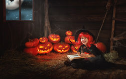 Halloween. child little witch with  pumpkin Jack  and magical bo Stock Images