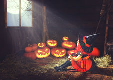 Halloween. child little witch with pumpkin  by the window waitin Royalty Free Stock Image