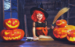 Halloween. child witch with broom,  pumpkin Jack  and magical bo Royalty Free Stock Photo