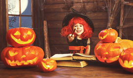 Halloween. child witch with  pumpkin Jack  and magical book of s Stock Photography