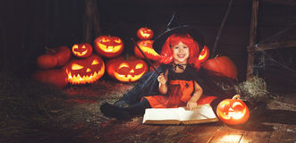 Halloween. child witch with  pumpkin Jack  and magical book of s Royalty Free Stock Photos