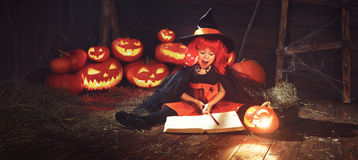Halloween. child witch with  pumpkin Jack  and magical book of s Stock Photos