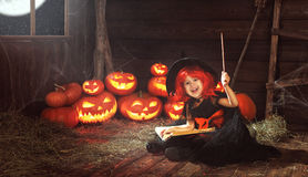 Halloween. child witch with  pumpkin Jack  and magical book of s Stock Images