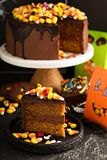 Halloween chocolate cake with candy on top. Halloween chocolate cake slice with candy corn and sprinkles on top and other holiday treats Stock Images