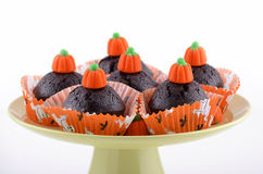 Halloween chocolate cupcakes. On pale green pedestal plate on white background in horizontal format Royalty Free Stock Images
