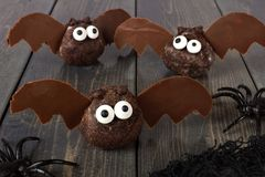 Halloween chocolate donut hole bats against dark wood Royalty Free Stock Image