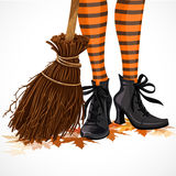 Halloween closeup witch legs in boots and with broomstick Royalty Free Stock Photo
