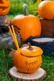 Halloween cocktail in pumpkin with Jack-o-Lantern in background. Close up.  Scary party punch. Halloween cocktail in pumpkin with Jack-o-Lantern in background Royalty Free Stock Image