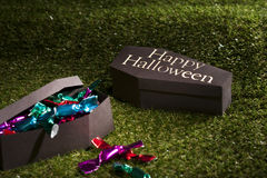 Halloween coffin on lawn with sweets Royalty Free Stock Images