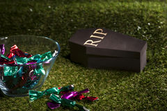 Halloween coffin on lawn with sweets Royalty Free Stock Photography