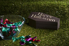 Halloween coffin on lawn with sweets Stock Image