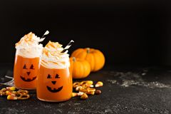 Halloween cold cocktail or drink with jack o`lantern face Stock Photos