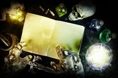 Halloween composition with mysterious bottles. And black magic book. Top view Stock Photography