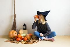 Halloween concept. Beautiful blonde girl in a witch hat with pumpkins and a broom on a white background royalty free stock images