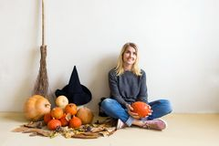 Halloween concept. Beautiful blond girl with a witch hat with pumpkins and a broom sitting on the floor against a white wall backg royalty free stock images