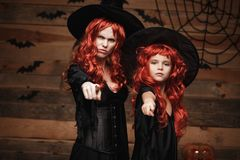 Halloween Concept - Beautiful caucasian mother and her daughter with long red hair in witch costumes with angry fussy facial expre. Ssion and pointing finger to stock image