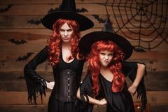 Halloween Concept - Beautiful caucasian mother and her daughter with long red hair in witch costumes with angry fussy. Facial expression stock photography