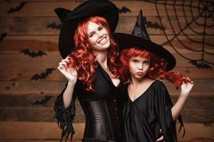 Halloween Concept - Beautiful caucasian mother and her daughter with long red hair in witch costumes celebrating Halloween posing. With over bats and spider web Royalty Free Stock Image