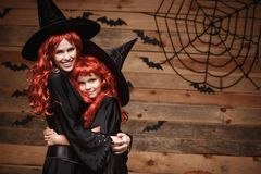 Halloween Concept - Beautiful caucasian mother and her daughter with long red hair in witch costumes happy smiling and hug each ot Royalty Free Stock Image