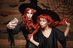 Halloween Concept - Beautiful caucasian mother and her daughter with long red hair in witch costumes taking a selfie with smartpho royalty free stock photo