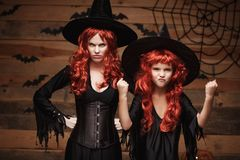 Halloween Concept - Beautiful caucasian mother and her daughter with long red hair in witch costumes witch cheerful fighting facia royalty free stock photography