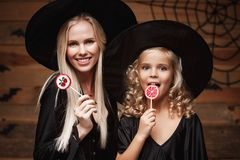 Halloween Concept - beautiful caucasian mother and her daughter in witch costumes celebrating Halloween with Halloween candy and s. Weet over bats and spider web royalty free stock image