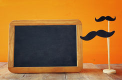 Halloween concept. Blank blackboard next to paper moustache Royalty Free Stock Photo