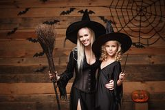 Free Halloween Concept - Cheerful Mother And Her Daughter In Witch Costumes Celebrating Halloween Posing With Curved Pumpkins Over Bats Royalty Free Stock Photography - 101888337