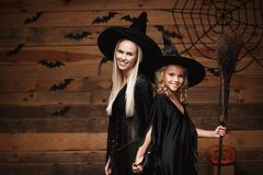 Halloween Concept - cheerful mother and her daughter in witch costumes celebrating Halloween posing with curved pumpkins over bats. And spider web on Wooden stock photo