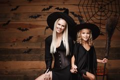 Halloween Concept - cheerful mother and her daughter in witch costumes celebrating Halloween posing with curved pumpkins over bats. And spider web on Wooden royalty free stock photography