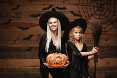 Halloween Concept - cheerful mother and her daughter in witch costumes celebrating Halloween posing with curved pumpkins over bats. And spider web on Wooden royalty free stock photo