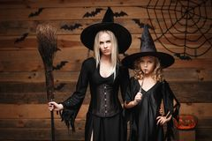 Halloween Concept - cheerful mother and her daughter in witch costumes celebrating Halloween posing with curved pumpkins over bats. And spider web on Wooden stock images